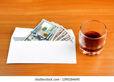 Envelope with an American Dollars and a Whiskey on the Table