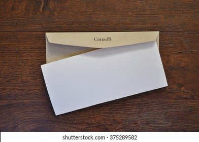 Envelope with Canada written in it and white folded paper
