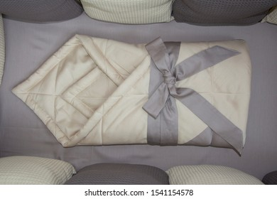 Envelope for the discharge of the newborn. Beige, brown bed linen in the crib. Folded blanket and bow. Close-up photo.