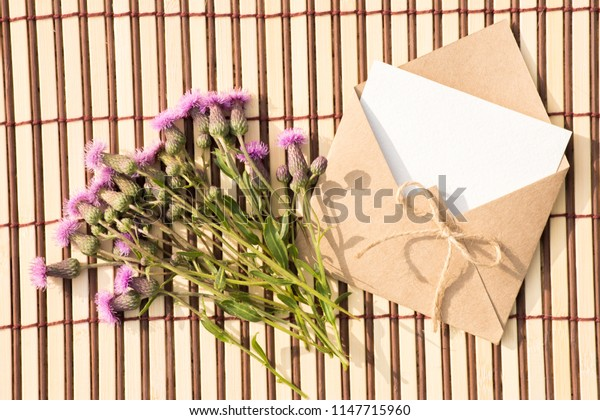 Envelope of kraft paper with a blank message and with beautiful lilac flowers