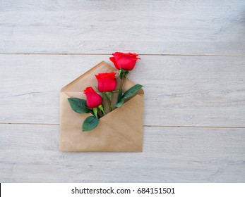 envelope of Kraft paper, with flowers red roses on a wood background, space for text, as congratulation wedding, birthday