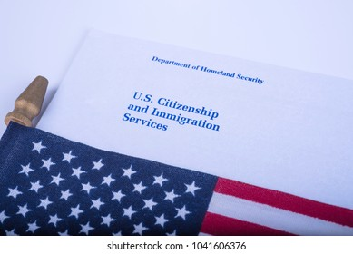 The envelope with Logo from US Citizenship and Immigration Services - USCIS (Department of Homeland security) near the Flag of United States of America. White Background.
