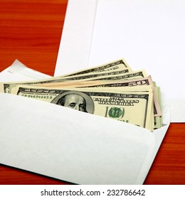 Envelope with a Money and Empty Paper on the Wooden Table closeup