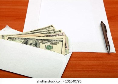 Envelope with a Money and Empty Paper for Text on the Wooden Table