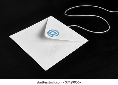 Envelope on black wood table with at Symbol, concept of E-Mail