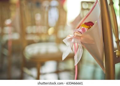 Envelope with rose petals and silk ribbons hangs from the chair