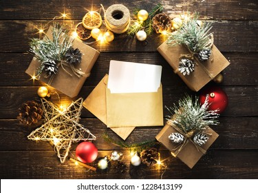 Envelope for santa claus with wreath made of Christmas decoration and christmas lights on dark wooden background top view flat lay Christmas background