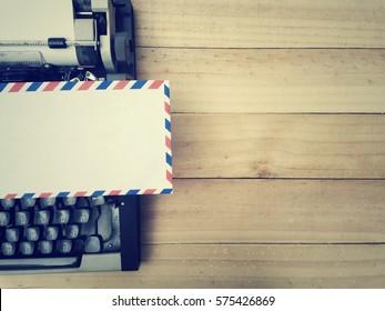 Envelope and typewriter on old wood table, process vintage tone