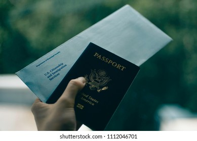Envelope from USCIS (United states citizenship and immigration Services) and Passport of USA in Hand, blurred toned on green and white background.