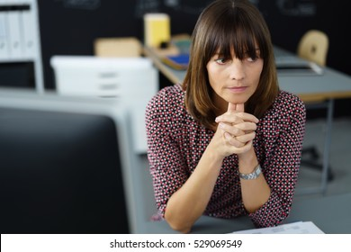 Envious businesswoman watching a colleague with an intense expression as she rests her chin on her hands looking to the side