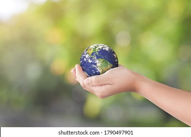 Environment day concept: Hand holding earth globe over blurred nature background. Elements of this image furnished by NASA