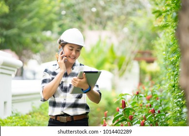 environment engineer, confident Young Asain woman engineer wearing white hardhat helmet and talking on mobile phone while working by green field smartphone and digital tablets for social networks,