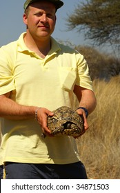 Environment protection volunteer holding a tortoise