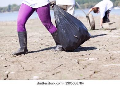Environmental activist is collecting waste at river or lake coast
