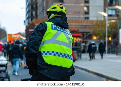 Environmental activists march in city. A police cyclist is seen on his bike from behind, wearing a high-vis vest and safety helmet during a street demonstration held by eco-activists, with copy-space