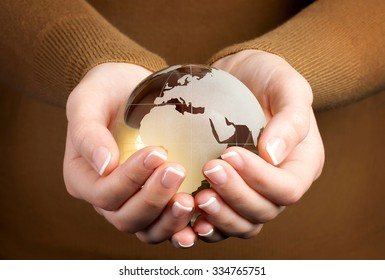 Environmental concept with brown glass globe in hand