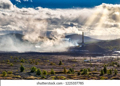 Environmental disaster. Copper plant in valley against the background of the mountains, toxic smoke from the pipes, dramatic rain clouds cut through the rays of the sun.