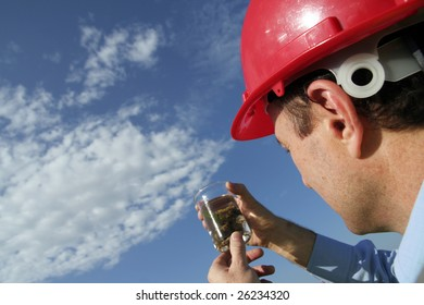 An environmental engineer examining a plant sample showing the beautiful blue sky, wearing a red safety helmet