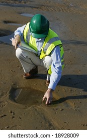 A environmental engineer on the mudflats collecting a sample of from the tidal puddle in front of him, showing the engineer wearing green hard hat and yellow reflective clothing