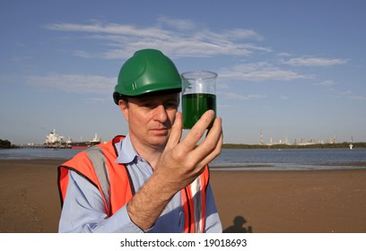 An environmental engineer on the mudflats examining a sample of oil from the ship docked behind him, showing the estuary and beautiful blue sky, wearing orange reflective vest and green safety helmet