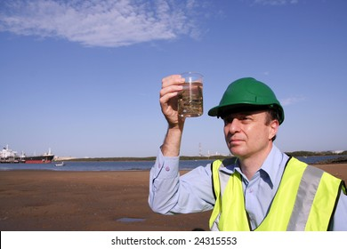 An environmental engineer on the mudflats examining an unusual  plant specimen found on the mudflats in the background is a tanker moored, wearing a yellow reflective vest and green safety helmet.