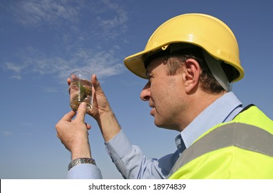 An environmental engineer, wearing protective clothing, and a yellow hard hard examining a sample into a specimen jar, with a beautiful blue sky behind him