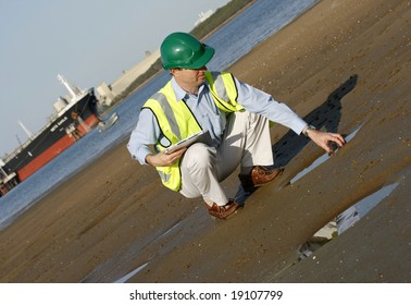 An environmental engineer, wearing protective clothing about to take a water sample, from the mudflats in the estuary.