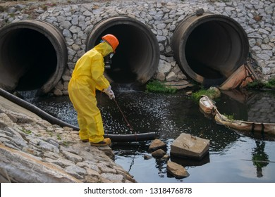 Environmental factory workers are checking oil stains from the factory effluent system. Pollution industry .