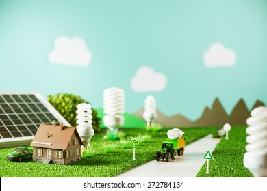 Environmental friendly toy town with model house, CFL lamps as trees and tractor carrying a light bulb