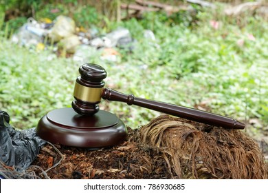 Environmental issue .Wooden gavel and block with black rubbish plastic and blurred pile of rubbish in the background.