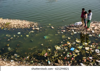 Environmental issues in India. Children playing near dirty littered with debris of the lake, watching the fish. Near the water Palace in Jaipur India. Photo taken 23 February 2017.