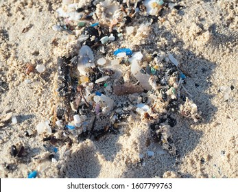 Environmental pollution. Sand beaches polluted with pieces of plastic waste. Micro plastics debris on the beach. Pieces of plastic residues