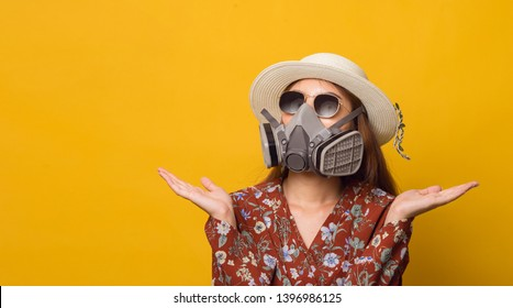 Environmental pollution that is affecting tourism in the future. Traveller young girl in red dress with pollution mask wearing glasses and wearing hat on yellow background.