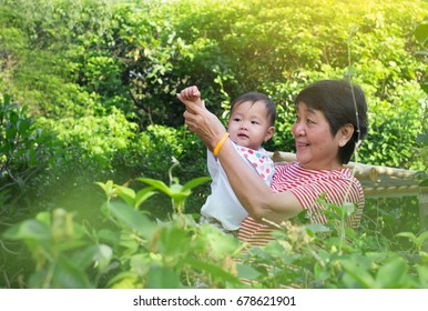 Environmental portrait of an Asian grandmother and her granddaughter in the garden showing upper body