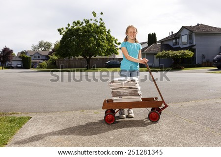 Environmental portrait of a young girl with her wagon delivering newspapers.