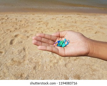 Environmentalist showing small pieces of placstic found on beach and sea water in his hand. These microplastics are harmful to marine animal lives and able to contaminate the food chain in the ocean.