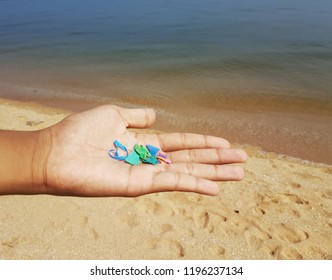 Environmentalist showing small pieces of plastic found on the beach. These microplastics are harmful to marine animals and polluting the ocean.