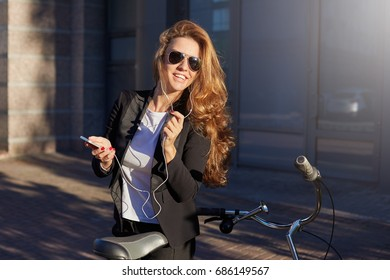Environmentally friendly female manager in formal suit and sunglasses reading report with serious face expression. Stylish attractive lady stops her bicycle on the way to office to make a phone call.