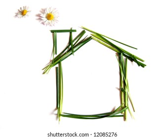 Environmentally friendly house made up of grass and daisies instead of smoke rising from the chimney, isolated on white