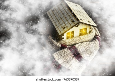 environmentally friendly warm home wrapped in a soft comfortable scarf. Snow is on the small house, snowstorm, snow. Concept of protection, warmth, coziness