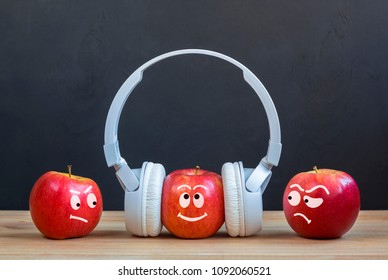 envy Creative concept. Abstract image with apples. One Apple in headphones standing in crowd stands out.
