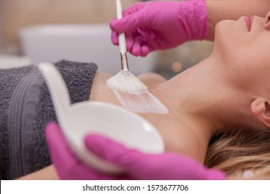 Enzyme peeling exfoliation treatment done by beautician cosmetologist on young woman's cleavage in beauty spa salon. Bright photo with peeling foam brush stroke. Healthy clear exfoliate skin co