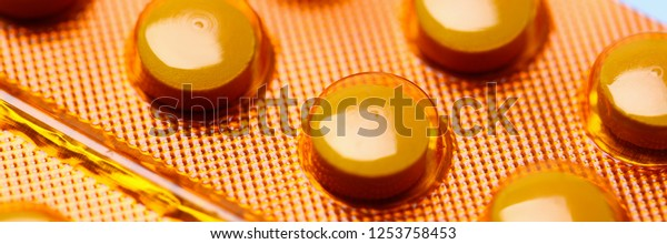 Enzyme tablets biologically active substances in orange packaging fake counterfeit drugs for cancer concept. Production and sale of pharmaceutical preparations plant for prescription pharmacy.