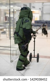 EOD officer in bomb protection suit take off the bomb bag with remote arm