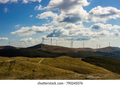 Eolic energy generators on the top of a hill and blue sky