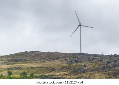 eolic renewable energy with wind turbines next to little chapel on a cloudy ble sky