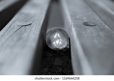 Eos cryptocurrency physical coin placed between the bench boards in black and white