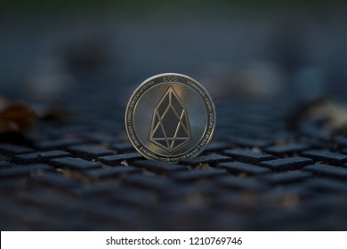 Eos cryptocurrency physical coin placed on a manhole