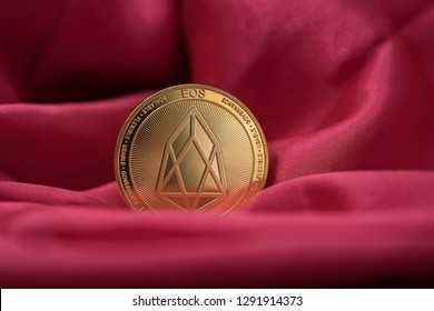 Eos cryptocurrency physical coin placed on red silk like material