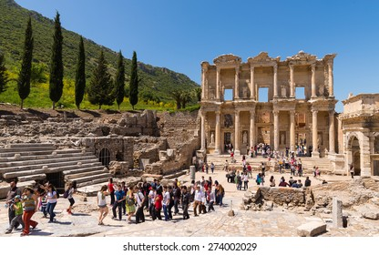 Ephesus, Turkey - April, 26, 2014: A group of tourists gather around a tour guide in the celsus library area of Ephesus in order to hear the guide tell them about the site